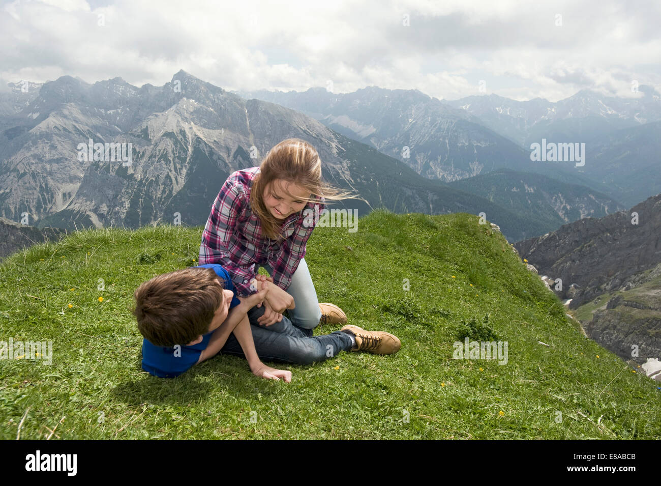 Young girl and boy playing wrestling on grass Alps Stock