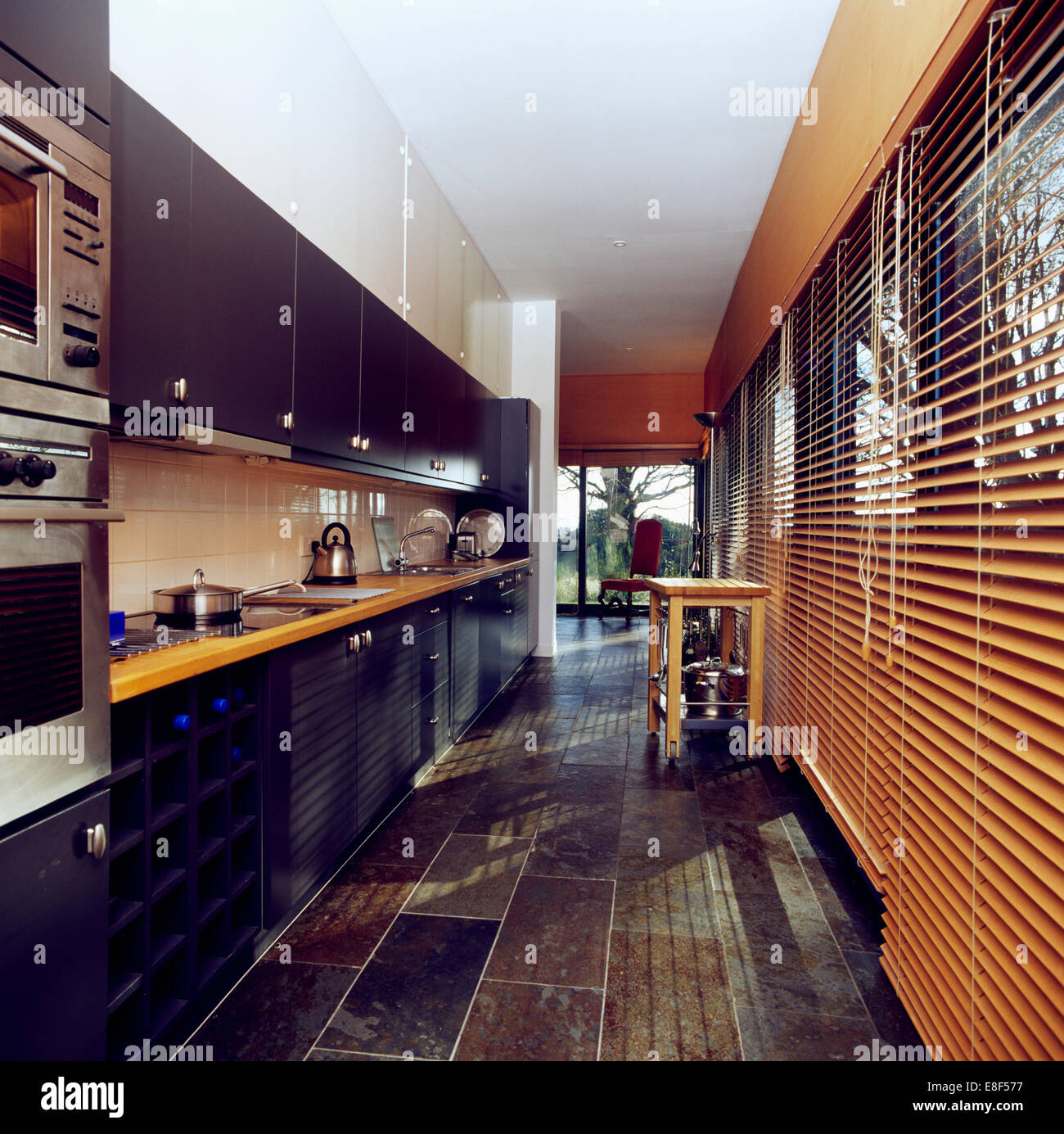 slate floor kitchen kidkraft toy and wooden venetian blinds in modern galley with worktops on black units