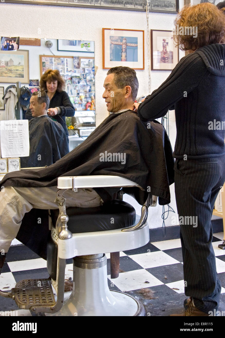 Female barber cuts mans hair in barbershop Stock Photo