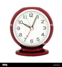Red alarm clock with luminous hands after 10 am in a ...