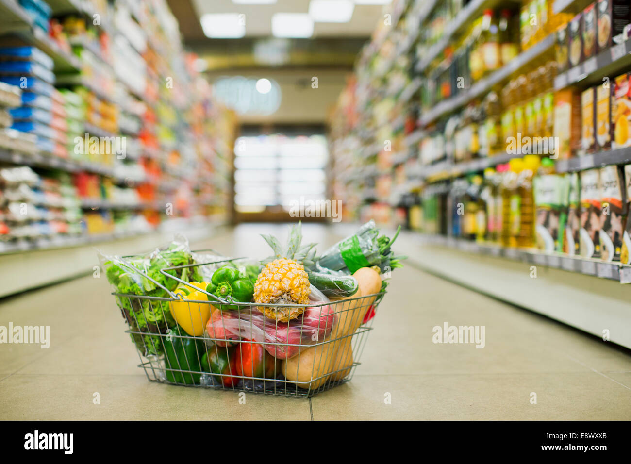 Close Up Of Full Shopping Basket On Floor Of Grocery Store
