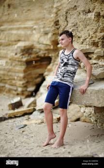 Teenage Boy Barefoot Sitting Rocks Cliff