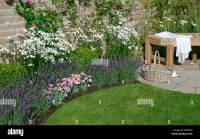 A flower border and seating in a corner of a walled ...
