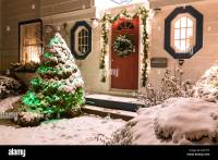 The front door of a snow covered family home decorated for ...