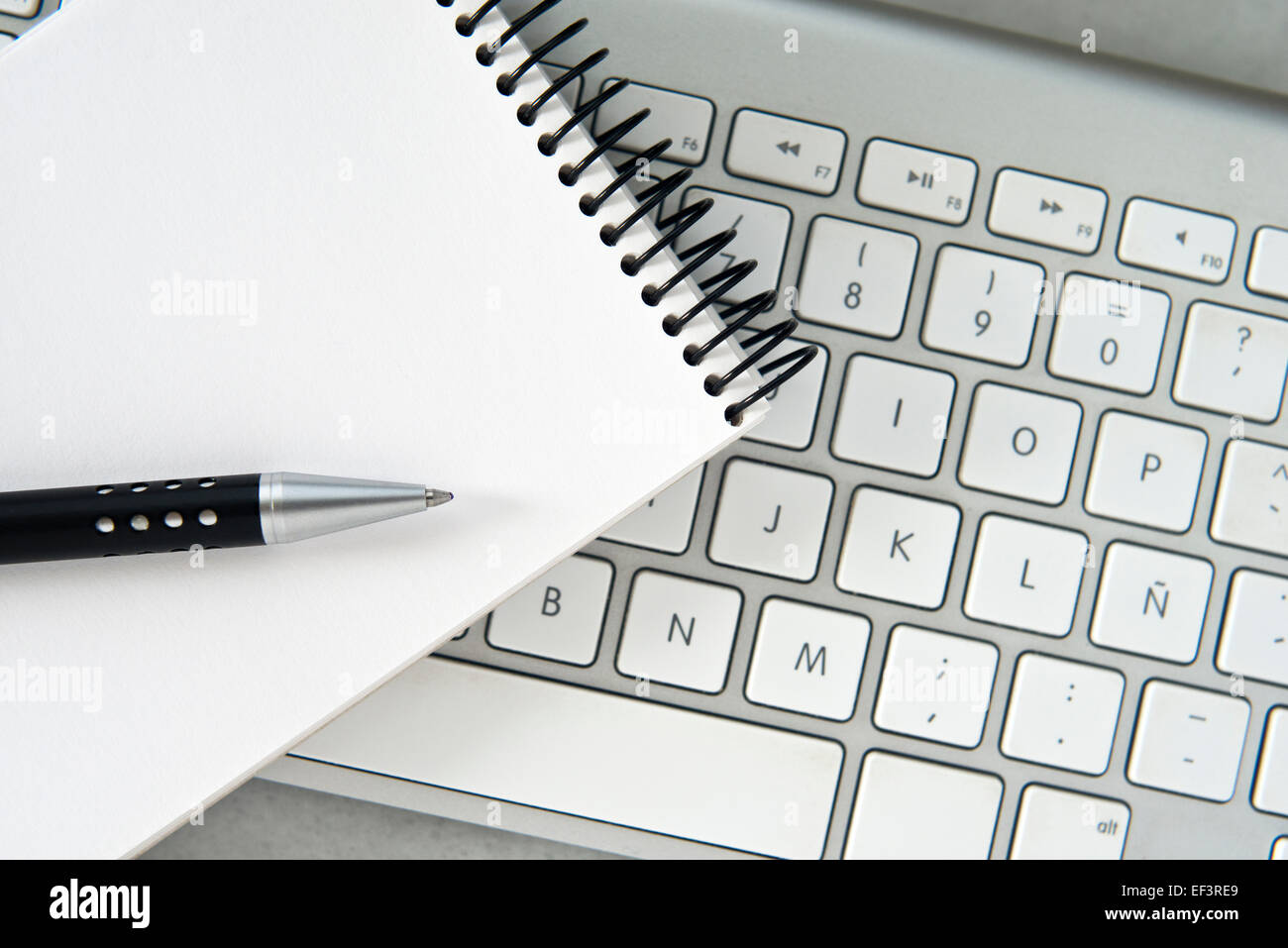 Notebook pen and computer keyboard background Stock Photo