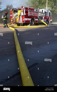 Water supply hose from a pumper fire truck at the scene of ...