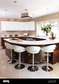 Bar stools at breakfast bar in modern kitchen, UK home