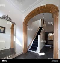 Wooden curved architrave with large mirror in entrance ...