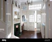 White entrance hall with green fireplace and dark wood ...