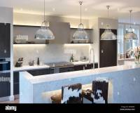 Modern kitchen with pendant lights above island unit ...