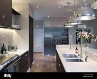 Modern kitchen with pendant lights above island unit ...