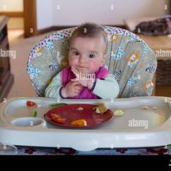 Baby Girl Chair Christmas Covers Pattern 8 Month Old Eating Food In High Stock Photo