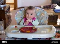 8 month old baby girl eating food in high chair Stock ...