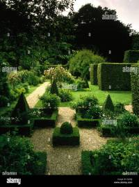 Box topiary on gravel area in large country garden in ...