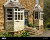 Front elevation of attractive old stone house with bay