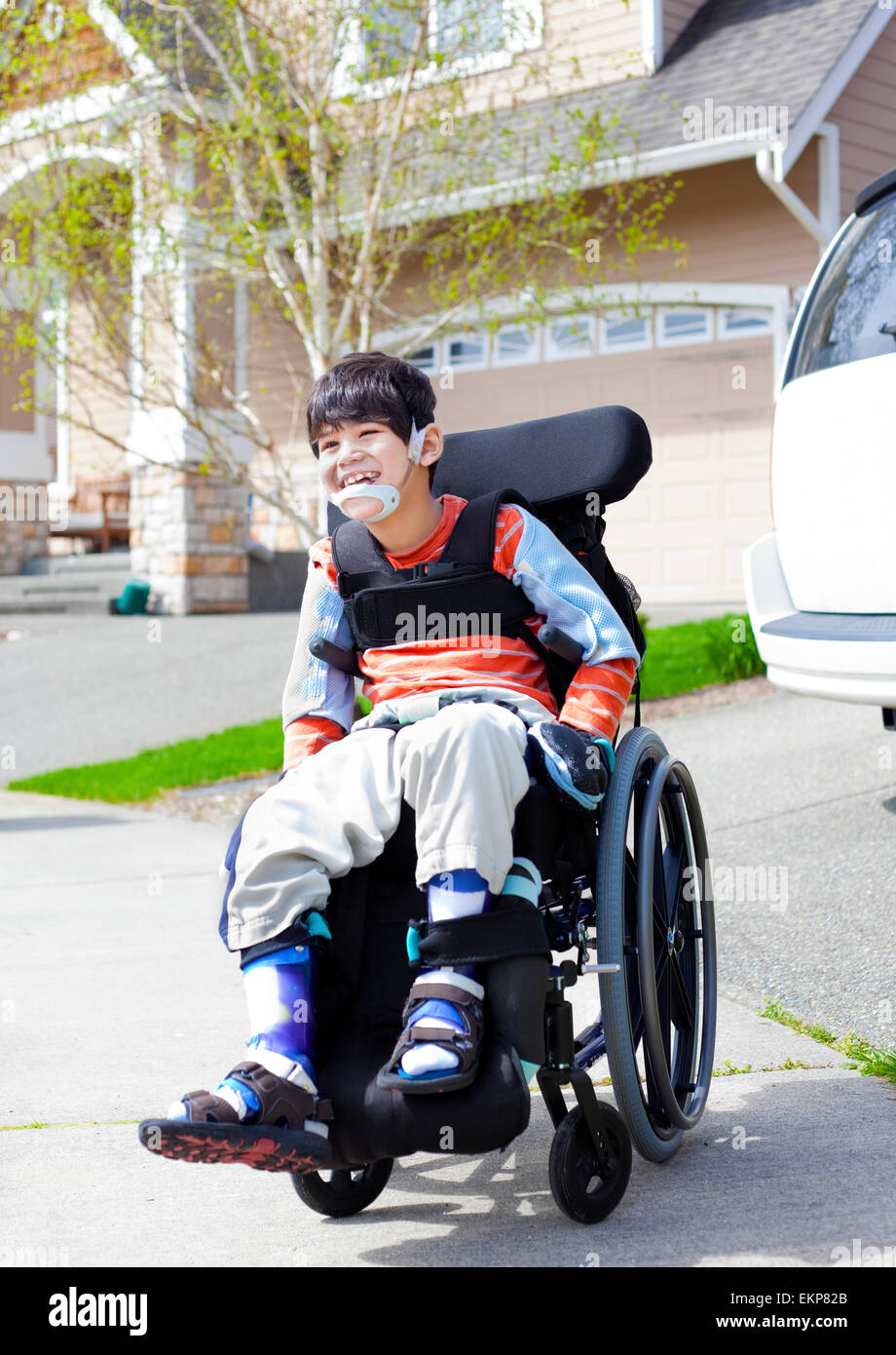 Happy little disabled boy in wheelchair Stock Photo