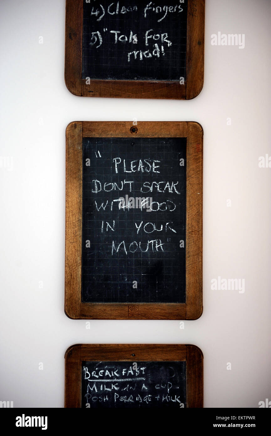 "A Set Of Chalk Boards On A Kitchen Wall With Shopping Lists, Memos's And A  House Rule Saying ""Please Don't Speak With Food In Yo"