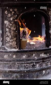 China, Tianjin, Fireplace with burning incense sticks ...