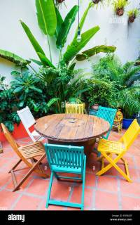 brightly coloured funky wooden chairs and table in garden ...