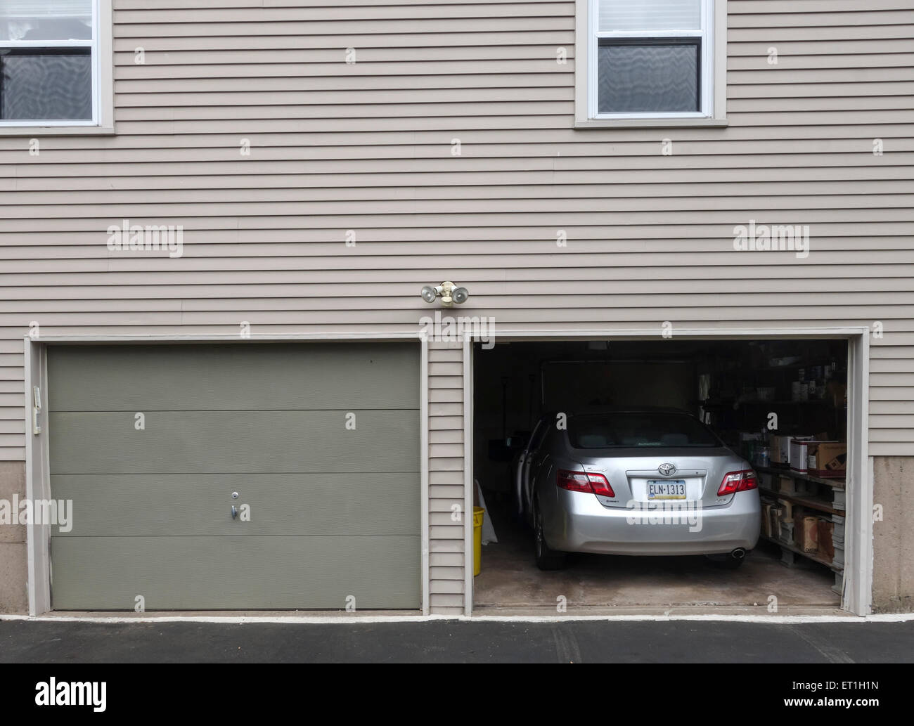 Open garage door with car parked inside american style