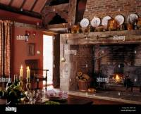 Plates on large rustic wooden beam above inglenook ...