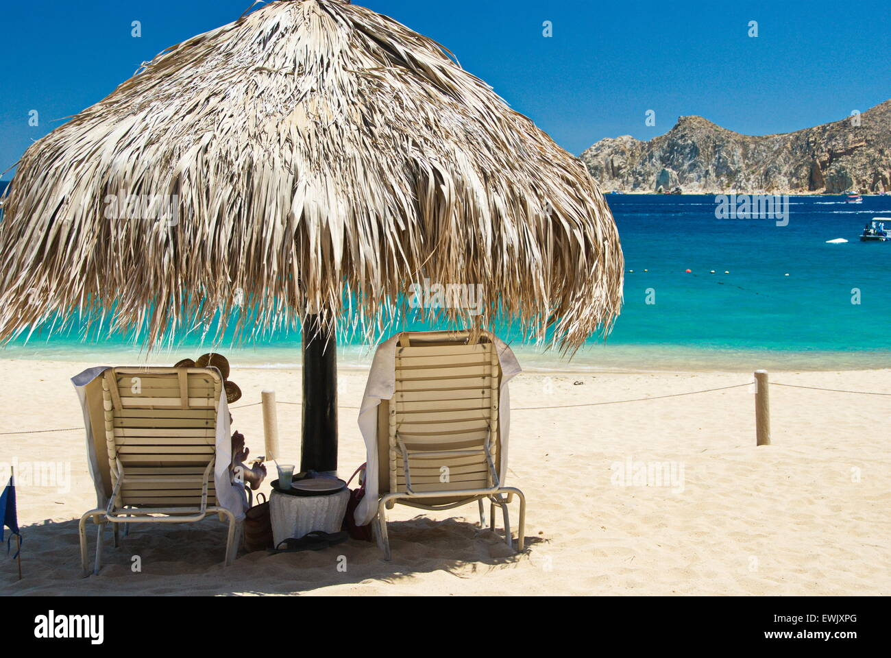 baja beach chairs baby relax lainey wingback chair and a half rocker person sitting on under palapa sunny day in