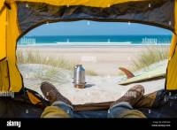 View from a tent on the beach with a surfboard, stove and ...