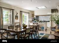 Antique dining table with chairs in open plan kitchen ...