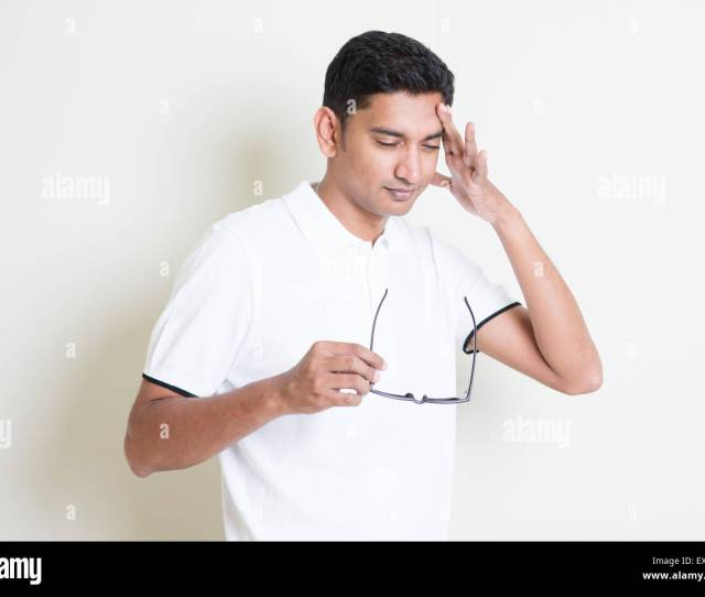 Portrait Of Tired Indian Guy Headache And Massage His Head Asian Man Standing On Plain Background With Shadow And Copy Space H