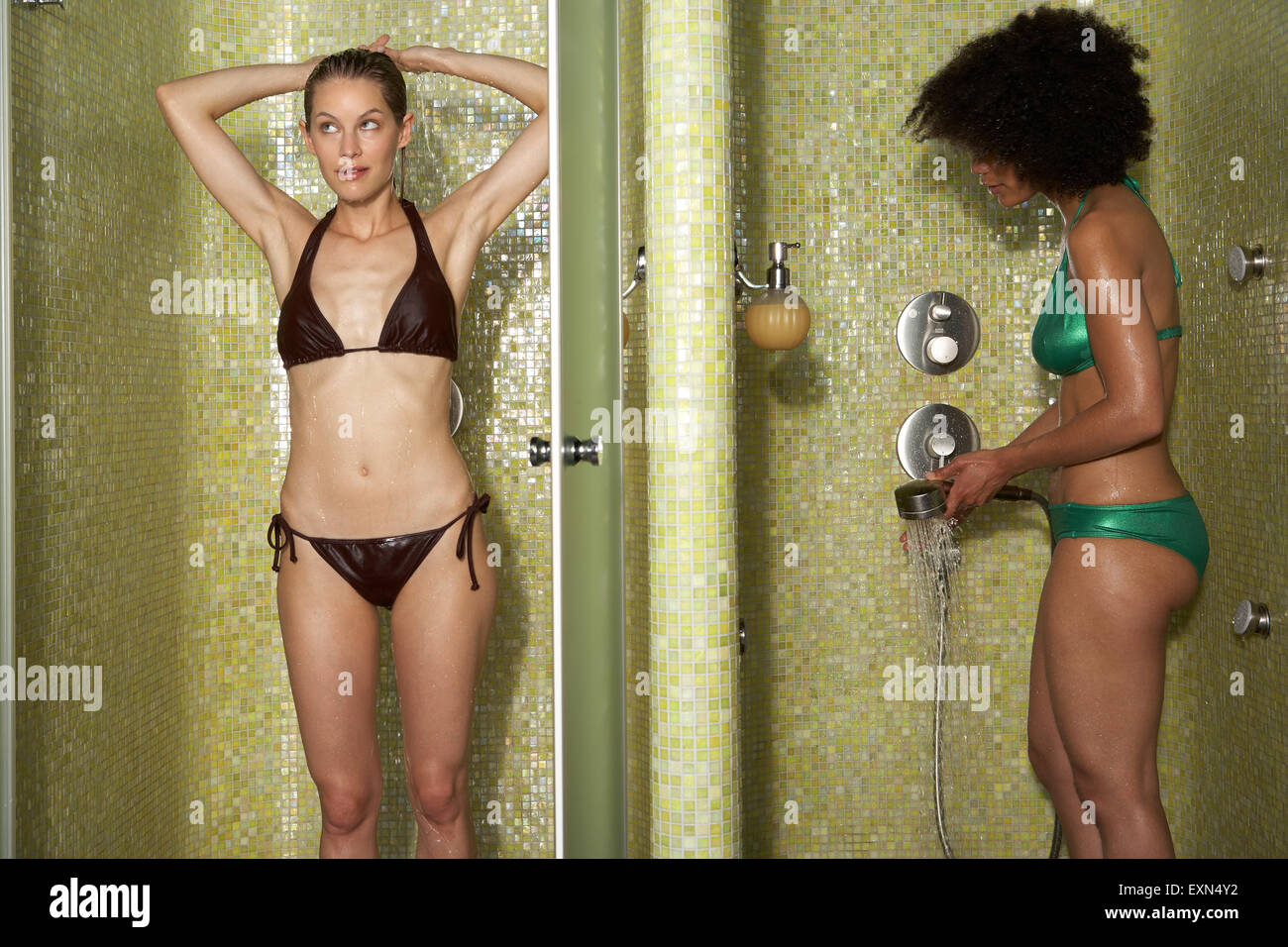 Two women standing in shower cabinets Stock Photo