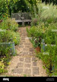 Small English cottage garden with paved and gravel path