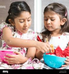 Indian girls sharing food, traditional snack murukku with each other. Asian  sibling or children living lifestyle at home Stock Photo - Alamy
