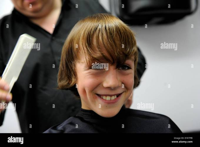 11 year old caucasian boy having a haircut in a barbers shop