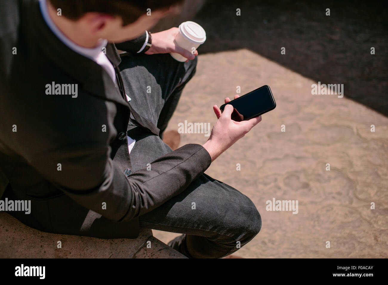Over The Shoulder View Of Young Businessman Reading