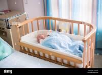 Newborn baby boy in bed. New born child sleeping under a ...