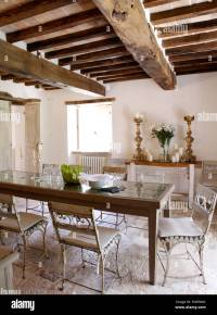 Old painted chairs at rustic wooden table in dining room ...