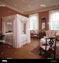 White drapes and linen on four poster bed in elegant