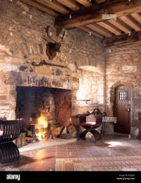 Lighted fire in fireplace in a medieval style hall in ...
