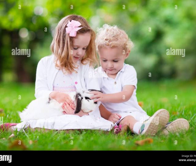 Children Play With Real Rabbit Brother And Sister At Easter Egg Hunt With White Pet Bunny