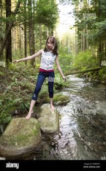Teenage Girl Walking Barefoot Over Rocks In Stream