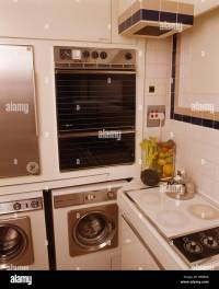 Wall mounted oven above washing machine and dryer in small ...