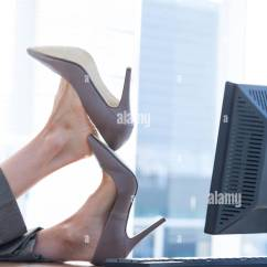 Swivel Chair Feet Camping With Cooler Businesswoman Sitting On Desk Stock Photo