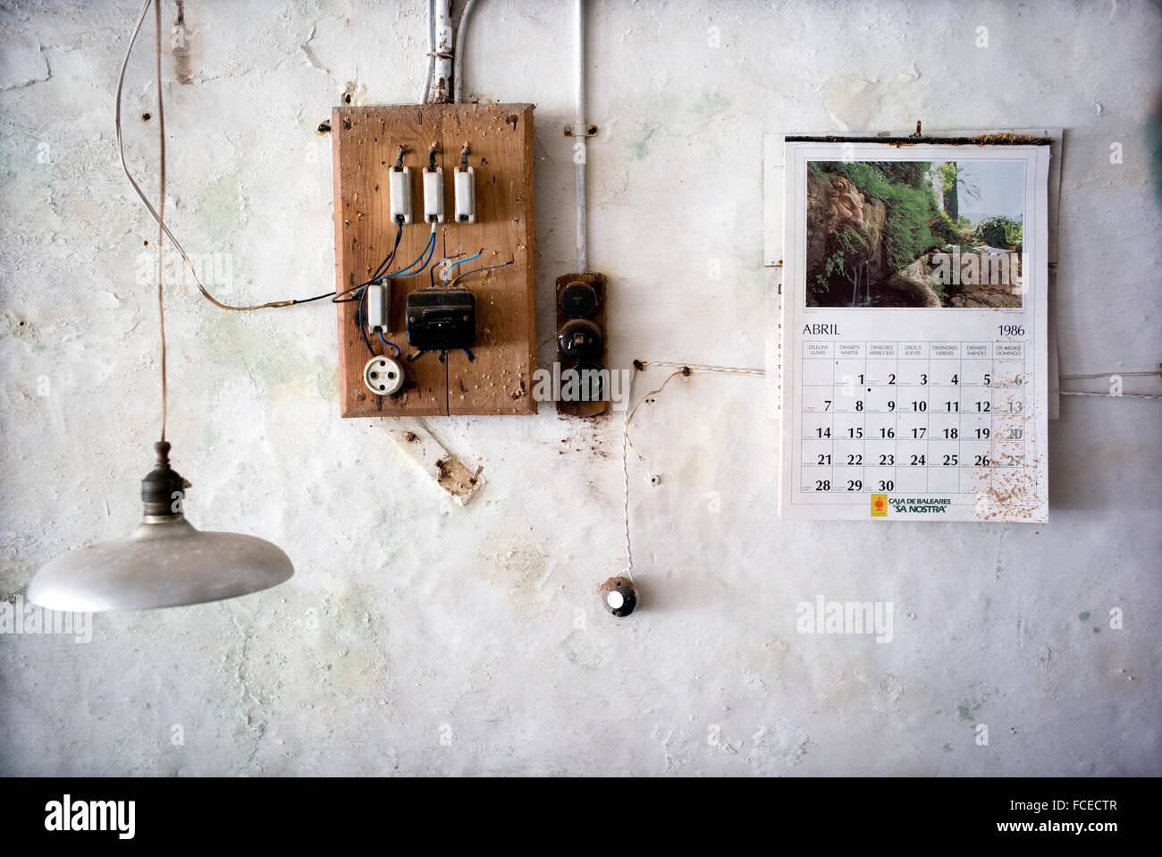 hight resolution of wall of an old workshop with an electrical fuse box and plug a calendar from april 1986 on the wall and a lamp hanging from