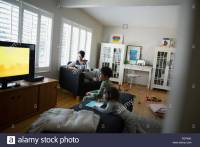 Family relaxing watching TV in living room Stock Photo ...