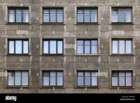 Many windows in row on facade of urban apartment building