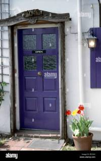 Close-up of a white house with a purple front door with a ...