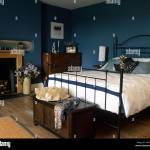 Black Wrought Iron Bed With White Duvet In A Blue Bedroom With A Hat Stock Photo Alamy