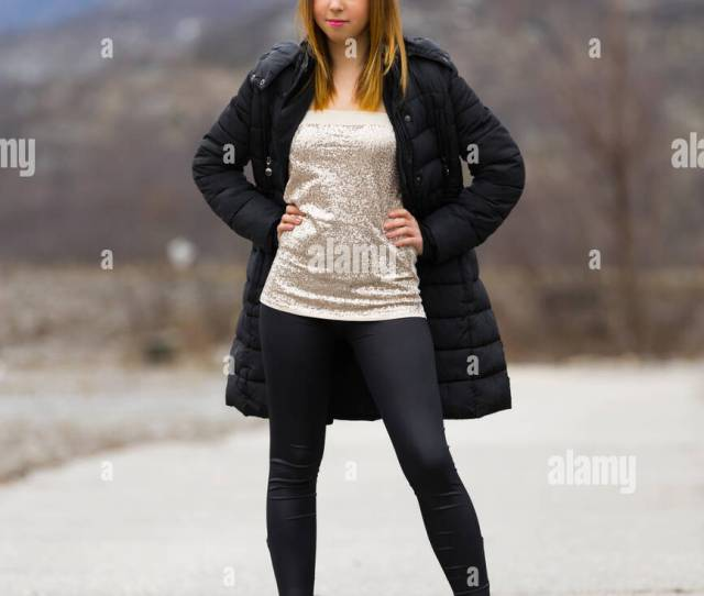 Attractive Teen Girl Posing Spread Legs Outdoors Hands On Hips Black Coat Winter Pose Firm Firmness Pants Low Boots Serious