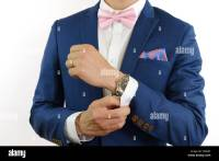 Man in blue suit with pink bow tie, flower brooch, and ...