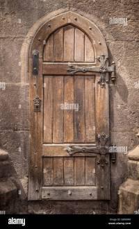 Ancient wooden door in stone castle wall Stock Photo ...